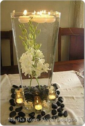 Submerged white Orchids with black river rocks stones and floating candles