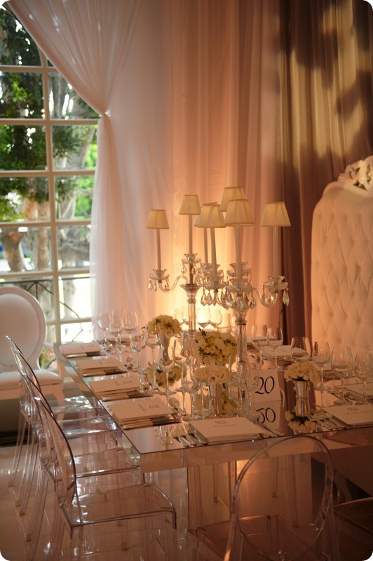 Glamorous wedding with ivory flowers and candelabra lampshades, mirage chairs, mirrored table tops and tufted bench seating