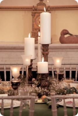 Round pillars on mix and match wooden candlestick holders are paired with votive holders with hurricanes for an eclectic look
