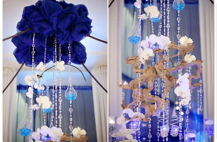 Love these hanging crystals and hanging votives intertwined with the natural heartiness of branches and white orchids.  The tufted navy blue ruffled canopy over the table.