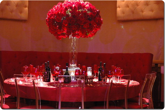 Tall Rose Centerpiece with red linens, red glasses and goblets, ghost chairs and red quilted tufted sofa bench