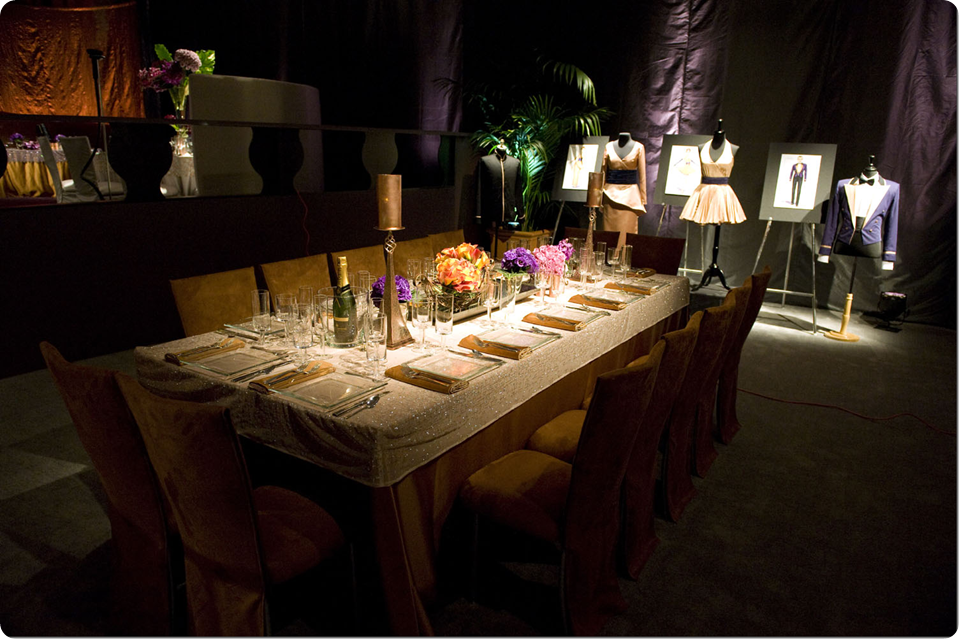 Long Rectangle  Table with Gold linens and white overlays with candles and low centerpieces