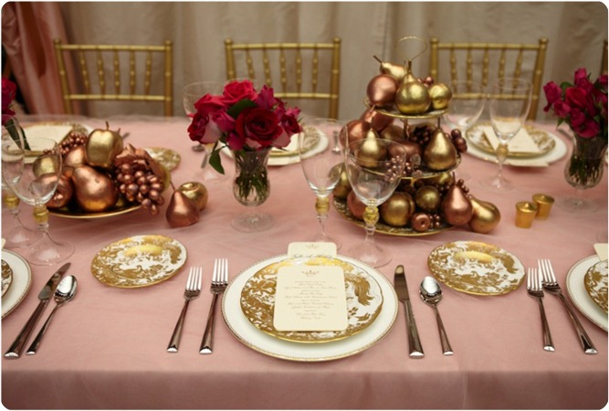 Gilded fruit in bronze and golden shades are stacked in tiered stands and in bowls for a striking look against soft linens