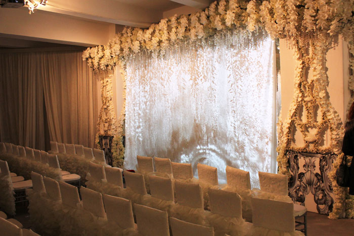 All white ceremony draped  with florals